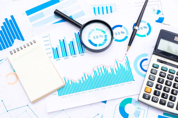 Calculator with Magnifying and Pen on Business Graphs finance document. Calculator with Magnifying and Pen on Business Graphs finance document. financial report stock pictures, royalty-free photos & images