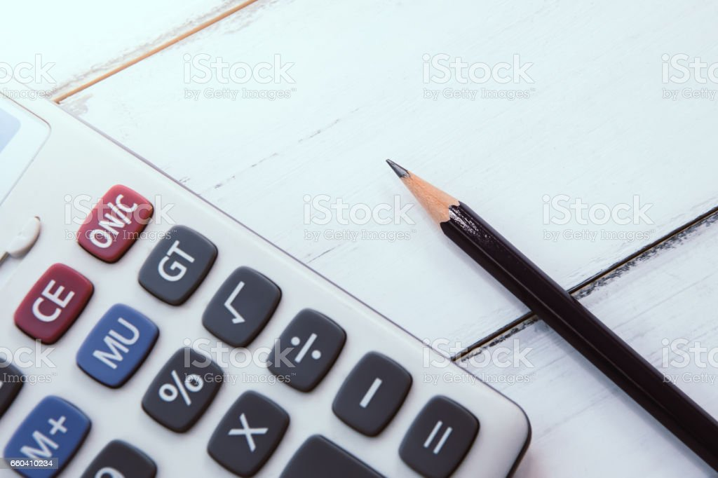 calculator with pencil on the wooden table background finance