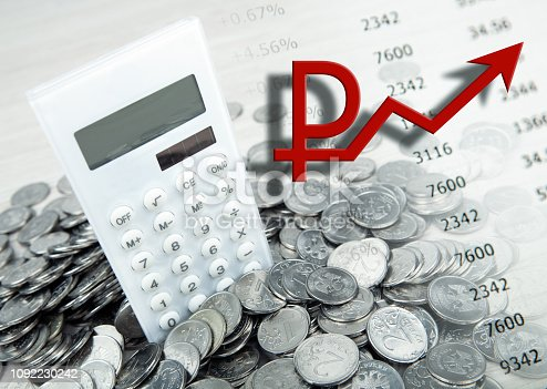 calculator with russian ruble coins and a symbol of the growing ruble