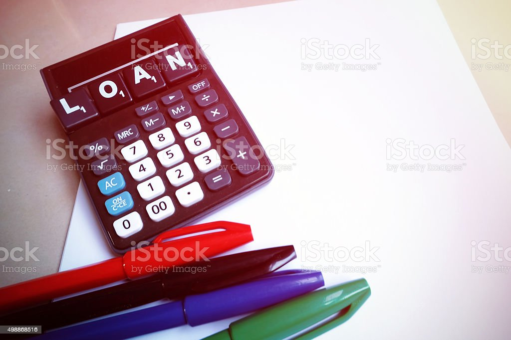 Calculator with the word loan  wooden block letters stock photo
