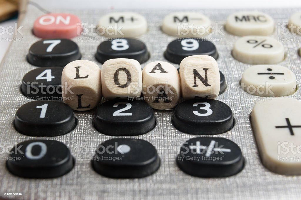 Calculator with the word loan written in wooden block letters stock photo