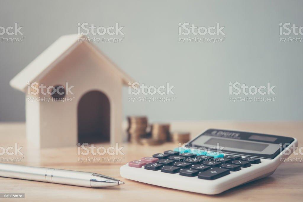 나무 집과 동전 스택 및 나무 테이블에 펜 계산기. 부동산 투자 및 집 모기지 금융 개념 - 로열티 프리 가격 스톡 사진