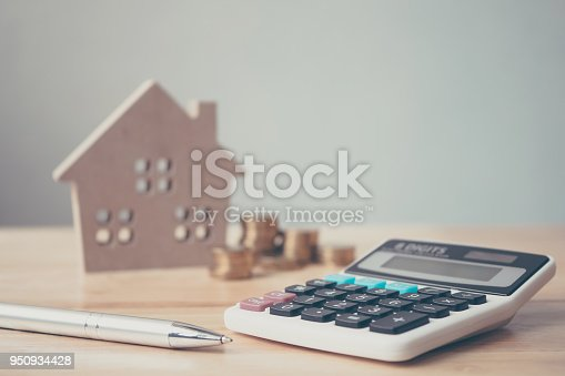 958039576 istock photo Calculator with wooden house and coins stack and pen on wood table. Property investment and house mortgage financial concept 950934428