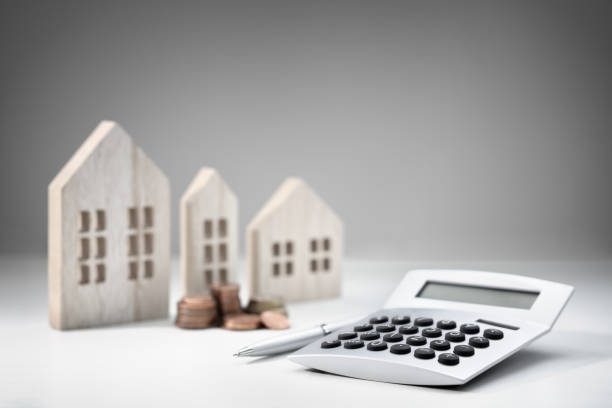 Calculator with wooden house and stack of coins stock photo