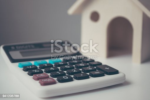 Calculator with wooden house on white table. Property investment and house mortgage financial concept