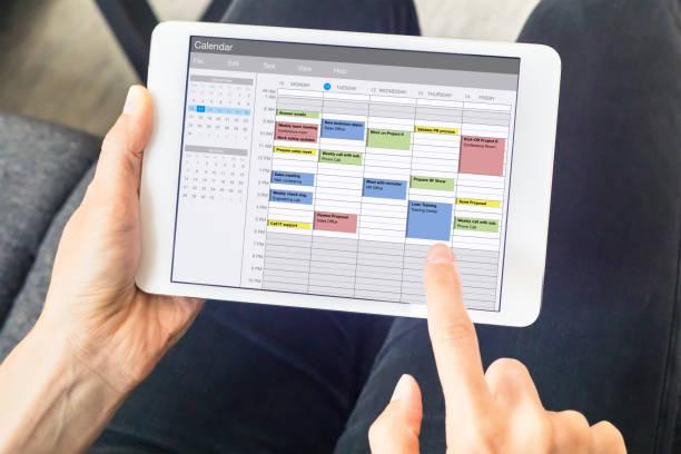 aplikacja kalendarz na komputerze typu tablet z planowaniem tygodnia z terminami, wydarzeniami, zadaniami i spotkaniami. urządzenie do trzymania rąk, koncepcja zarządzania czasem, organizacja planowania godzin pracy, harmonogram - czas zdjęcia i obrazy z banku zdjęć