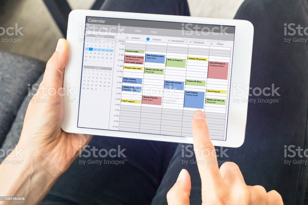 Calendar app on tablet computer with planning of the week with appointments, events, tasks, and meeting. Hands holding device, time management concept, organization of working hours planner, schedule stock photo