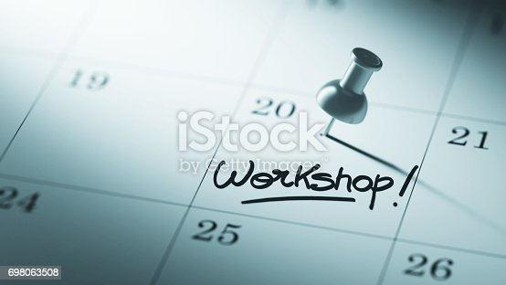 Concept image of a Calendar with a push pin. Closeup shot of a thumbtack attached. The words Workshop written on a white notebook to remind you an important appointment.