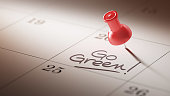 Concept image of a Calendar with a red push pin. Closeup shot of a thumbtack attached. The words Go Green written on a white notebook to remind you an important appointment.