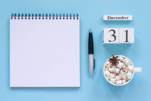 calendar December 31 cup cocoa and marshmallow, empty open notepad stock photo