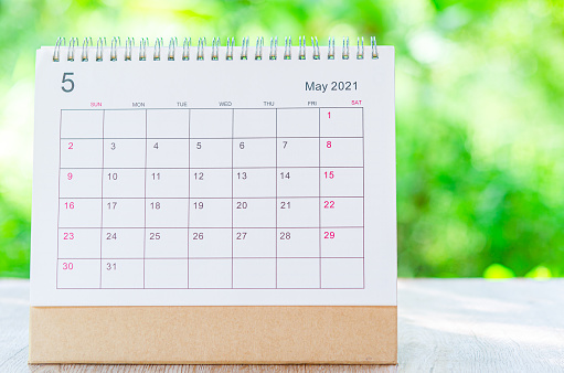 Calendar desk 2021 May month for organizer to plan and reminder on wooden table on nature background.