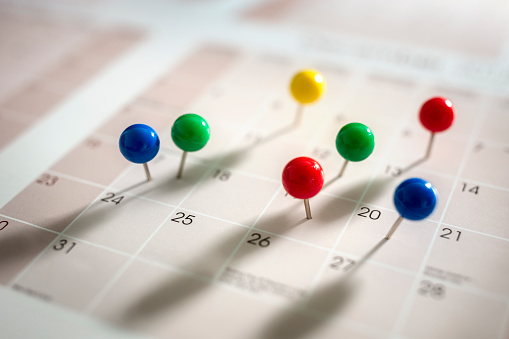 Thumbtack pins in calendar concept for busy, appointment and meeting reminder