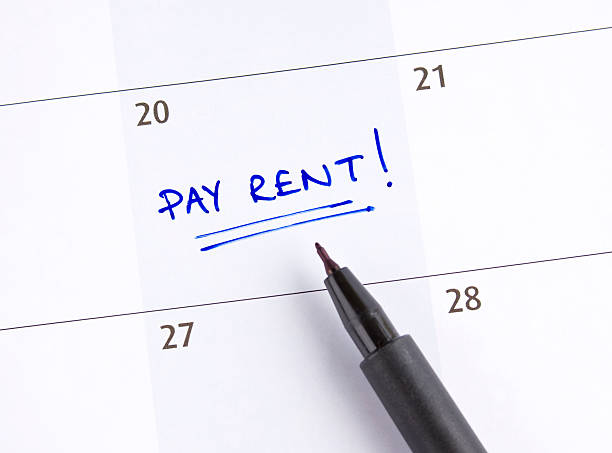 A calendar marked pay rent! on the 20th of the month stock photo