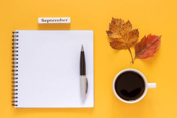 kalendermonat september, tasse kaffee, leere notizblock mit stift und herbstblätter auf gelbem hintergrund. mockup top-ansicht flache vorlage für ihr design, einladung, postkarte. konzept zurück zur schule - unterrichtsplanung vorlagen stock-fotos und bilder