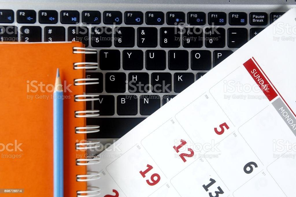 Calendar, notebook and a laptop computer stock photo