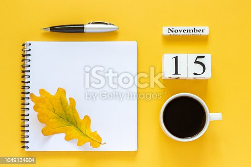 868951648 istock photo calendar November 15 cup of coffee, notepad with pen and yellow leaf on yellow background 1049134604