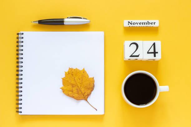calendrier novembre 24 tasse de café, le bloc-notes avec le stylo et la feuille jaune sur fond jaune - nombre 24 photos et images de collection