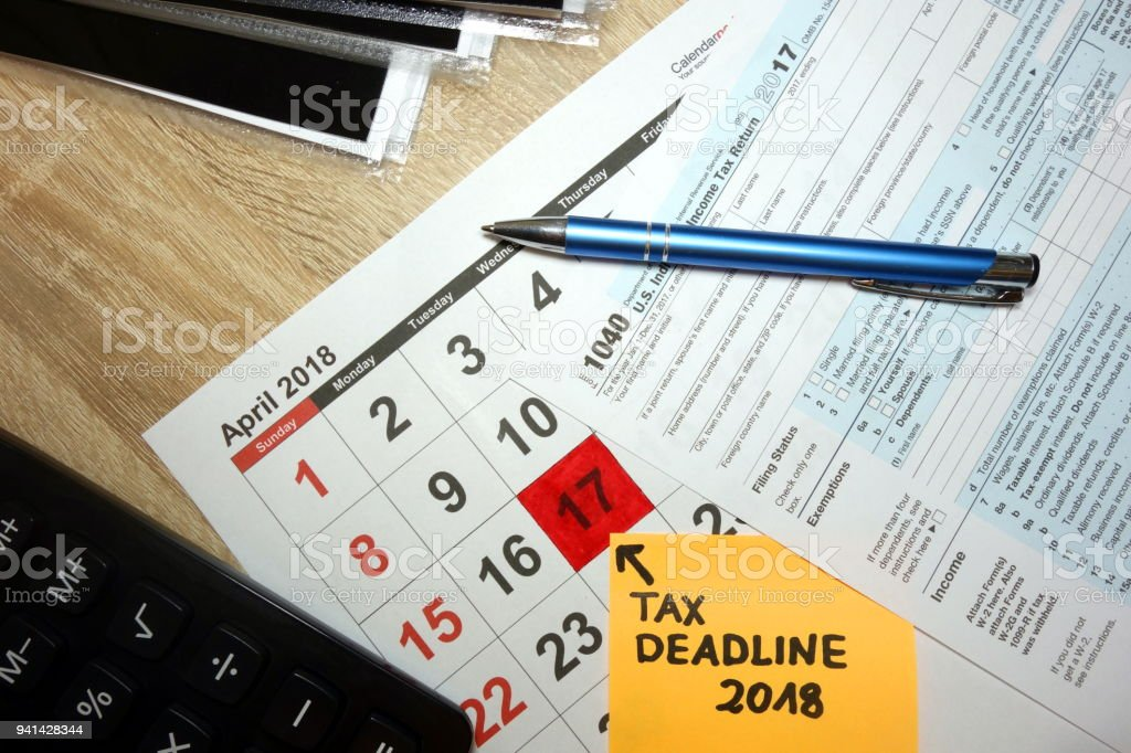 Calendar on desk showing tax day for filing forms - april 17 2018 stock photo