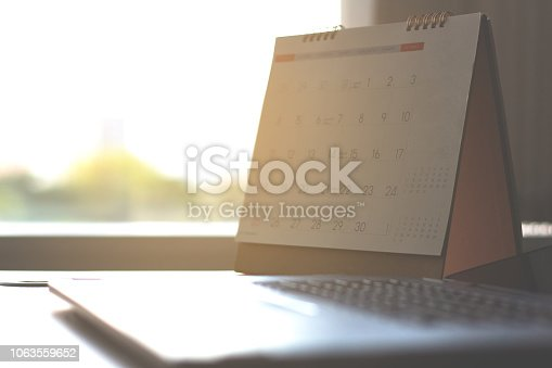 istock calendar on desk table and laptop keyboard city view background . 1063559652