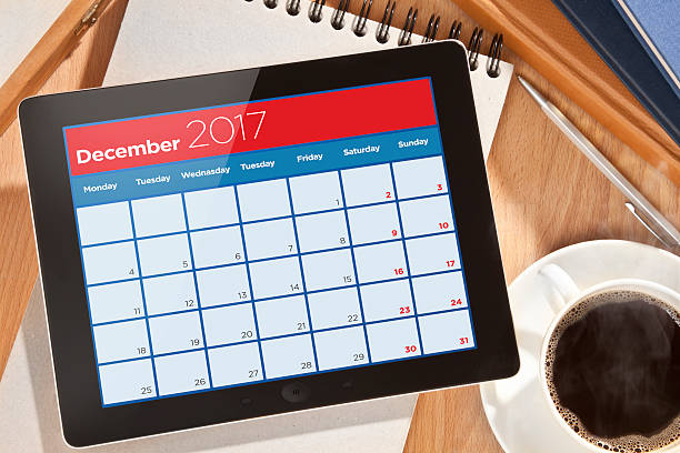 calendar on digital tablet - december stock photos and pictures