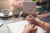 On 2019 Calendar book,Female'hand of planner writing daily appointment.Woman mark and noted schedule(holiday trip) on diary at office desk.Calendar reminder event for planner concept