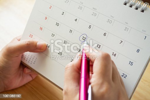 calendar page with female hand holding pen on desk table