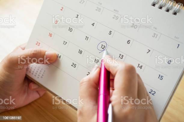 Calendar page with female hand holding pen on desk table picture id1061085192?b=1&k=6&m=1061085192&s=612x612&h=w3tz9fvdpuxnahkdpz3x1bl3emhktmyxnzgfak11oy4=