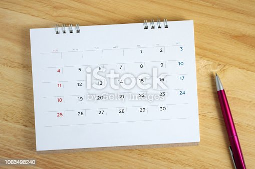 istock Calendar page with pen on wooden desk table 1063498240