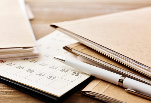 Pile of papers paperwork and dead line. Calendar on office wooden desk table. With copy space.