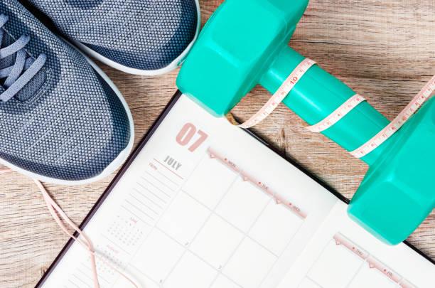kalender-plan mit grünen hantel und sneakers - trainingstagebuch stock-fotos und bilder
