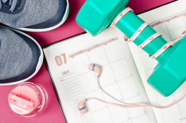 kalender plan med gröna hantel och sneakers - calendar workout bildbanksfoton och bilder