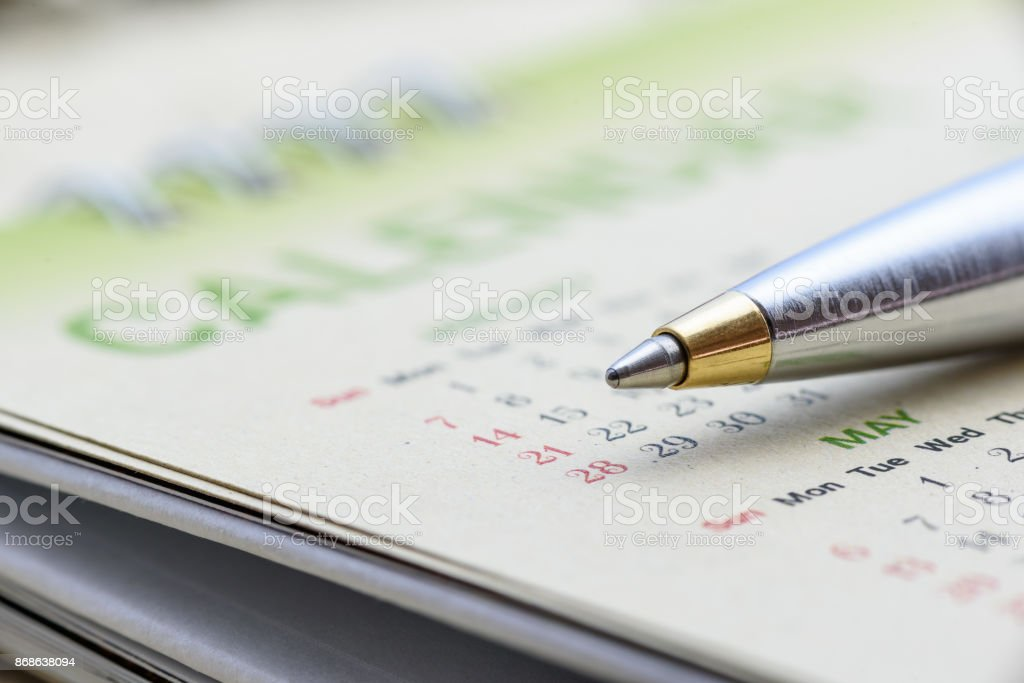Calendar planner stationery concept : Blue metal pen on a paper desk calendar. A calendar is a system of organizing days for commercial or administrative purposes by giving names to a period of time. stock photo