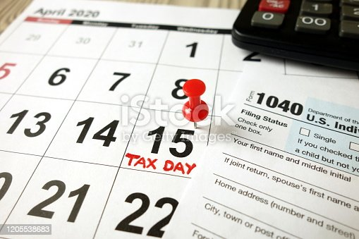 istock Calendar showing date April 15 2020, 1040 form and calculator 1205538683