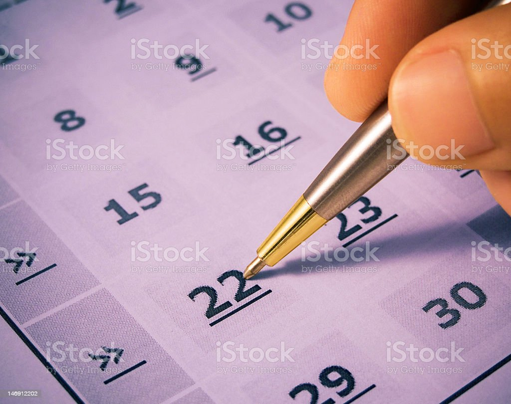 Calendar with a gold pen pointing at the 22nd stock photo