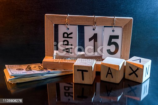 947260978 istock photo Calendar with date 15th April and cubes with word 'tax' 1125908276