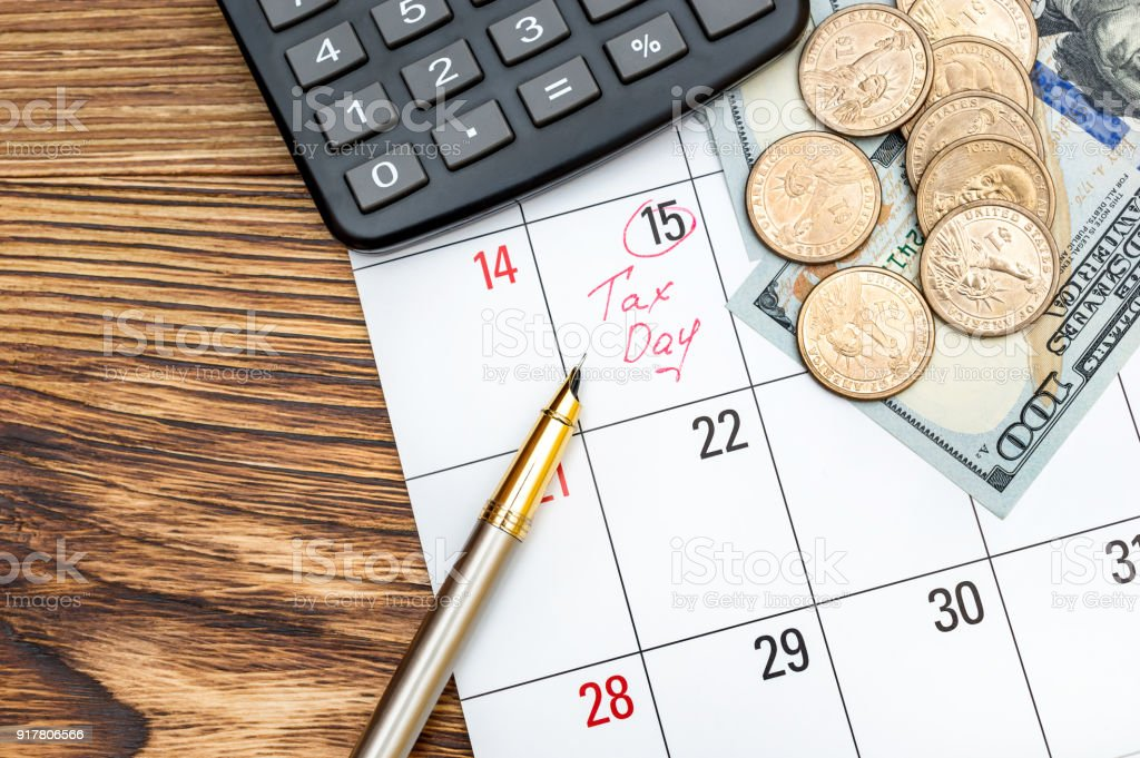 calendar with inscription tax day money and calculator on the table