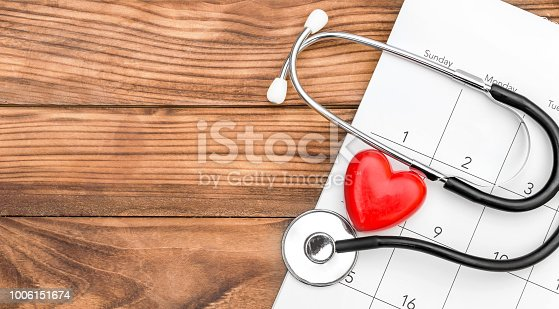 Calendar with stethoscope and red heart on wooden background. Space for text.