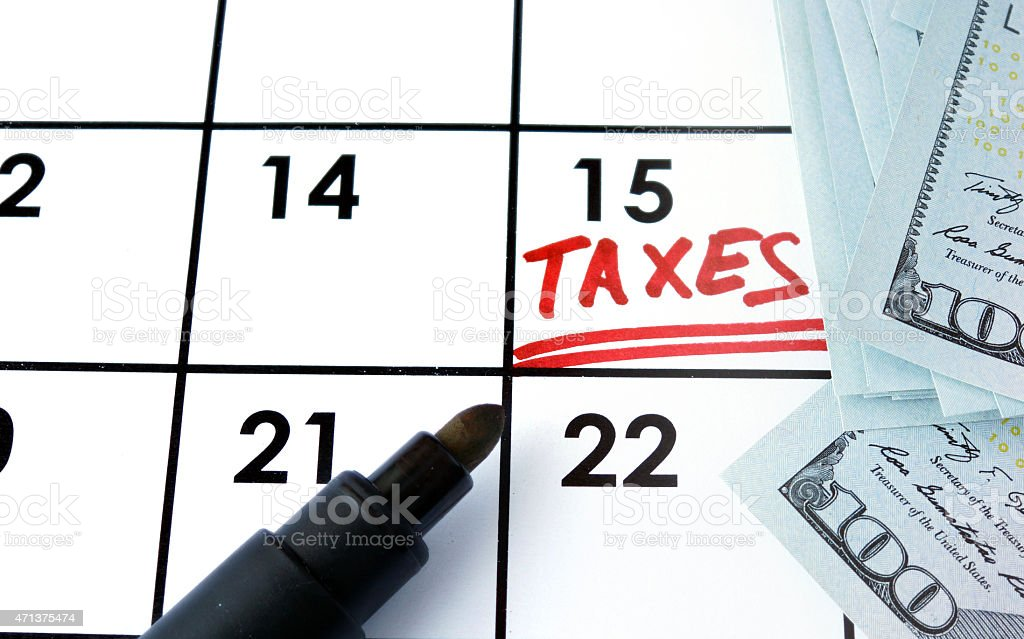 Calendar with word taxes and dollars notes. stock photo