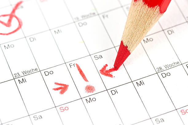 calender - ausrufezeichen bei termin am freitag mit rotem stift - holiday calendars stock pictures, royalty-free photos & images