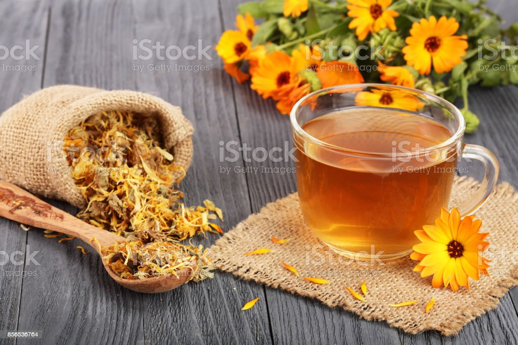 Calendula tea with fresh and dried flowers on black wooden background stock photo