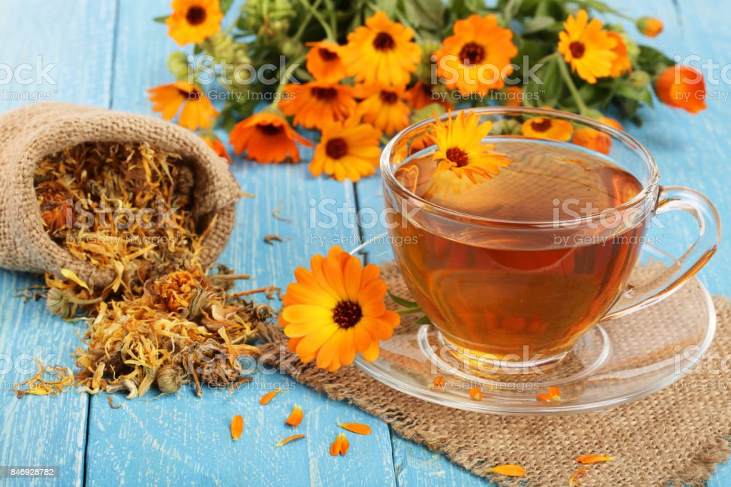 Calendula tea with fresh and dried flowers on blue wooden background stock photo