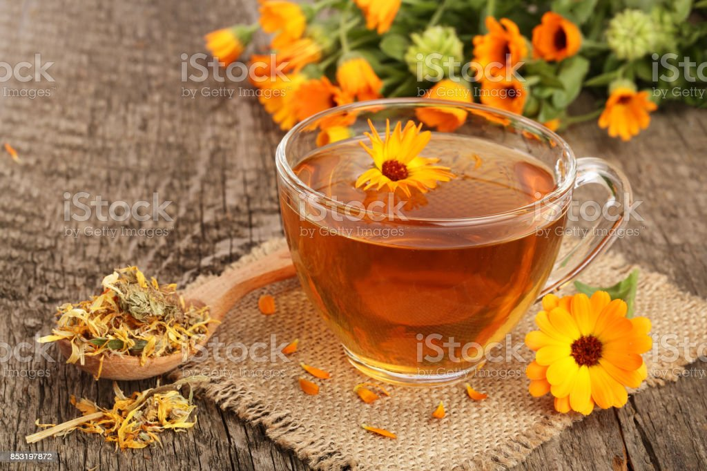 Calendula tea with fresh and dried flowers on old wooden background stock photo