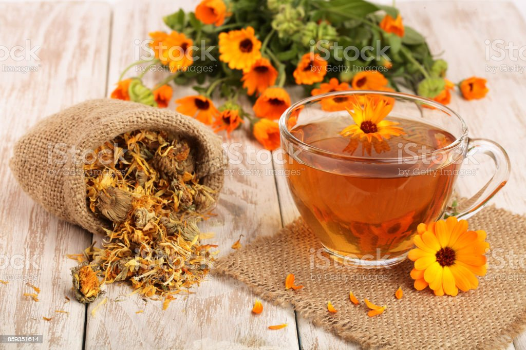 Calendula tea with fresh and dried flowers on white wooden background stock photo