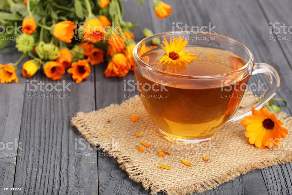 Calendula tea with fresh flowers on black wooden background stock photo