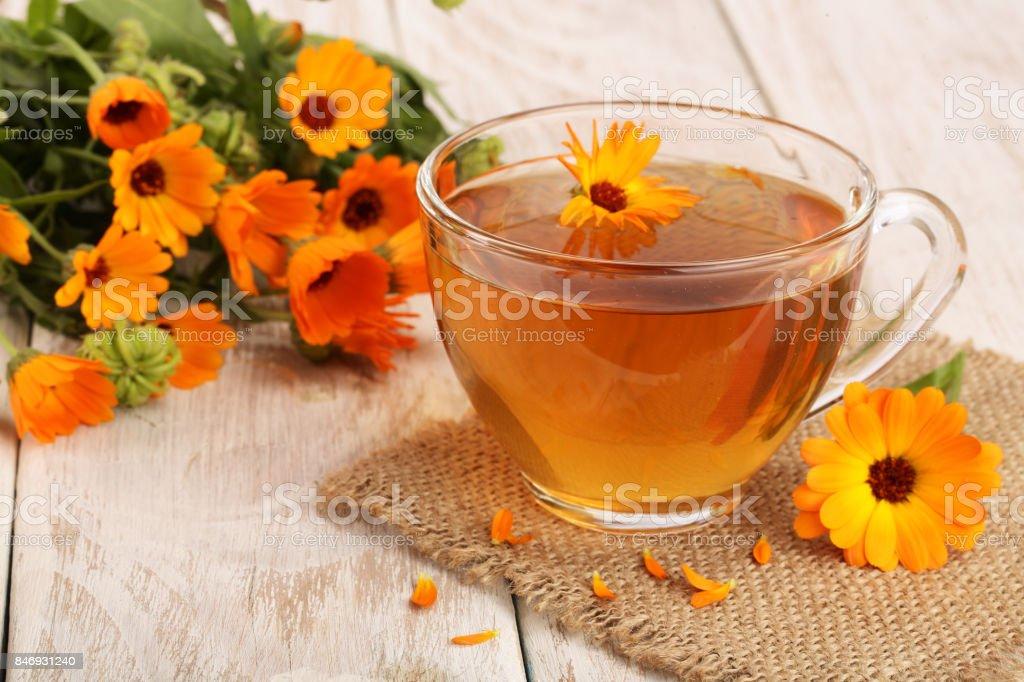 Calendula tea with fresh flowers on white wooden background stock photo