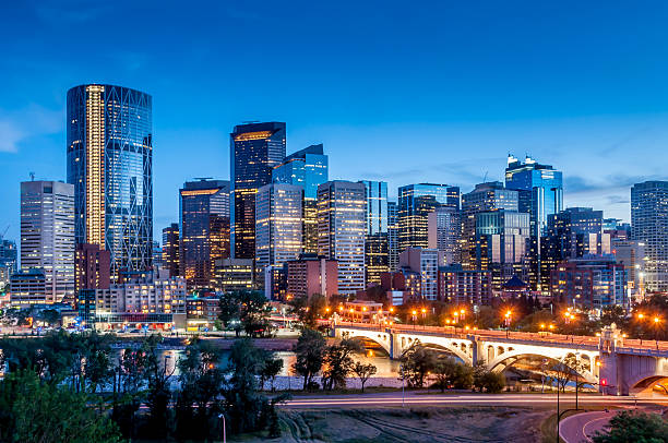 Calgary skyline Calgary skyline at night with Bow River and Centre Street Bridge. alberta stock pictures, royalty-free photos & images