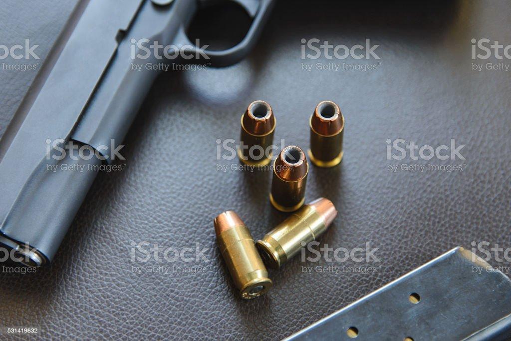 .45 Caliber hollow point bullets near handgun and magazine stock photo