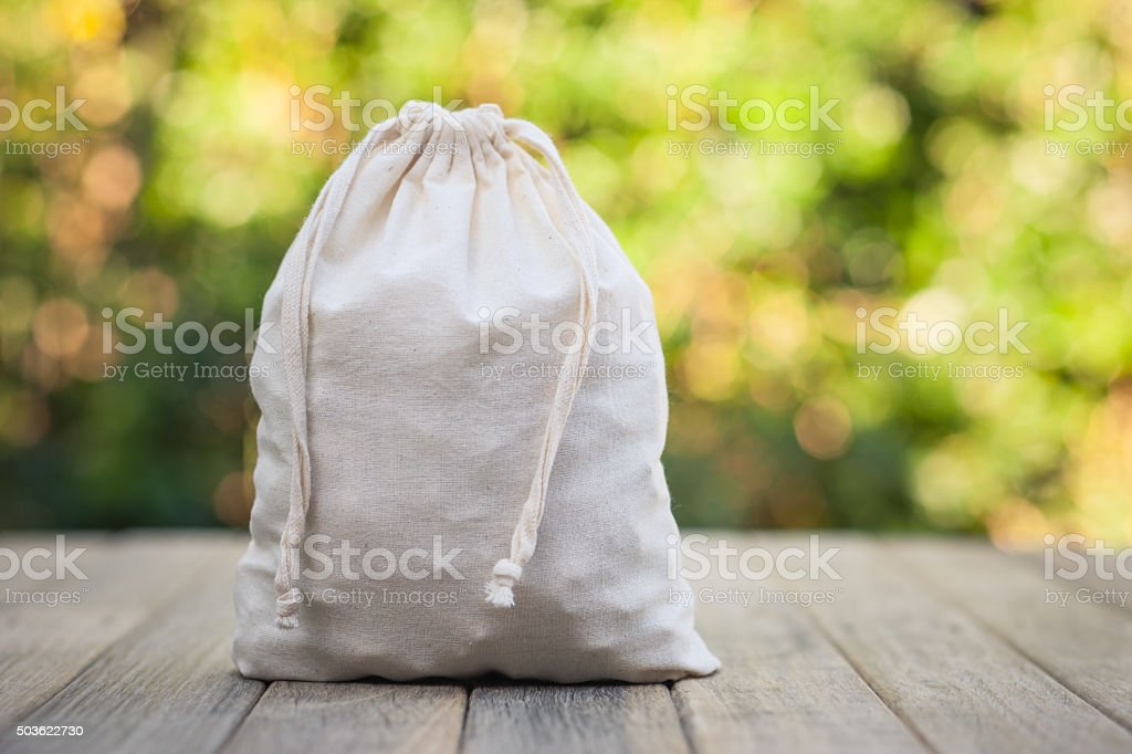 Calico Bag Sitting on Rustic Timber Bench stock photo