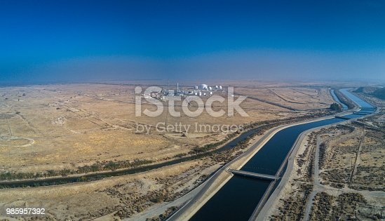 Drone shot of an oil field in the California Central Valley, near Bakersfield, with the Kern River and the California Aqueduct crossing the arid landscape.