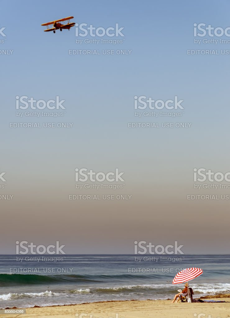 California beach scene with beach goer under umbrella and biplane flying above. stock photo